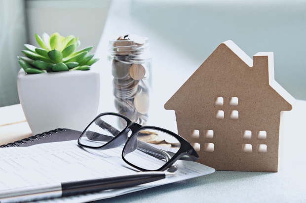 photo shows glasses, a pen, a figurine of a house, a plan, papers, and a glass of coins sitting on a sunny tabletop