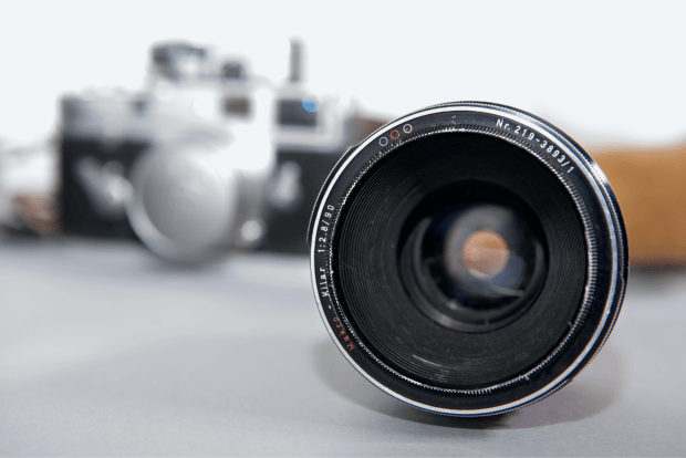 photo shows a camera in the background out of focus and a lens in the foreground in focus