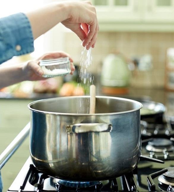 0 Woman adding pinch of salt in cooking pot on stove