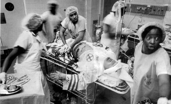 Grayscale: Hospital emergency-room, a Grand Wizard of the Ku Klux Klan lies in his white Klansmen robe and white connical hat on a gurney.  He's bleeding from the abdomin.  Five members of an all black medical staff--nurses and doctors surgical grab--are hurriedly and intently attending to him--apparently, to save his life.
