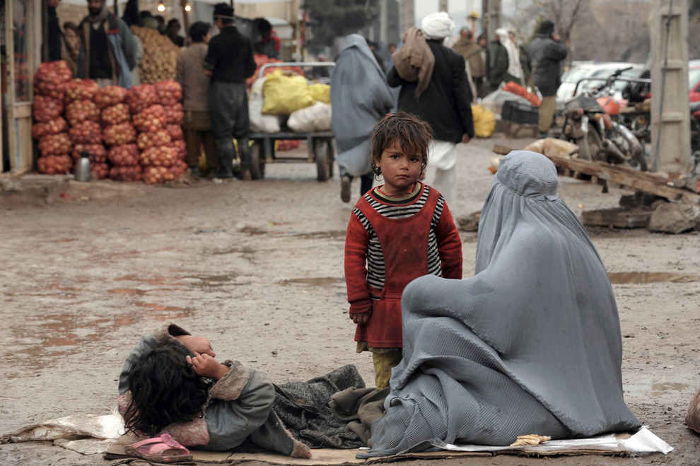 An Afghan beggar sits on the ground on a street in Herat, Jan. 8 ,2013. Over a third of Afghans are living in abject poverty. (Aref Karimi/AFP/Getty Images)