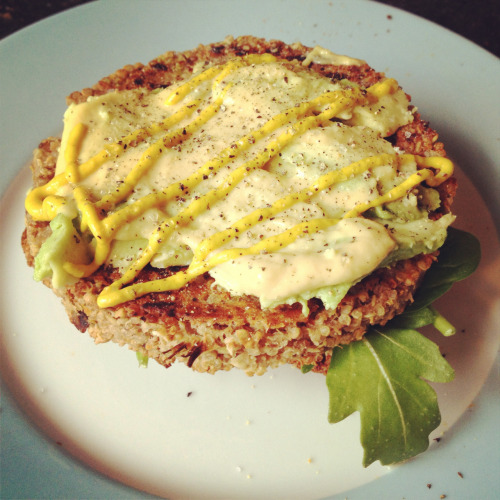 Vegan burger on whole wheat toast with hummus, spinach, avocado, creole seasoning, mustards, salt and pepper.