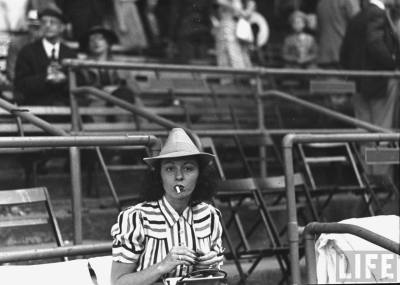 The Brooklyn Dodgers manager's wife Nellie Durocher, sitting on the bleechers smoking a cigarette (1939).