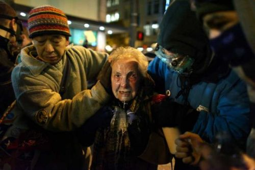 "carton-rouge:  84-year-old Occupy Seattle participant Dorli Rainey, pictured above after being pepper sprayed by Seattle Police on November 15th. She later wrote about the incident: ""Something funny happened on my way to a transportation meeting in Northgate. As I got off the bus at 3rd and Pine I heard helicopters above. Knowing that the problems of New York would certainly precipitate action by Occupy Seattle, I thought I better check it out. Especially since only yesterday the City Government made a grandiose gesture to protect free speech. Well free speech does have its limits as I found out as the cops shoved their bicycles into the crowd and simultaneously pepper sprayed the so captured protesters. If it had not been for my Hero (Iraq Vet Caleb) I would have been down on the ground and trampled. This is what democracy looks like. It certainly left an impression on the people who rode the No. 1 bus home with me. In the women's movement there were signs which said: ""Screw us and we multiply.'"""