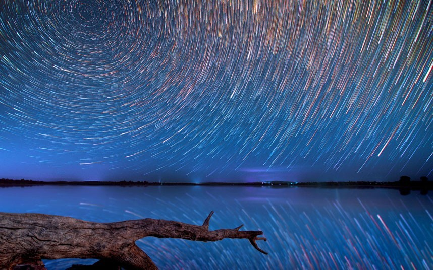 The night sky over a water landscape with a tree branch. The stars in the sky are blurs of light, so that together they look like a ring of circles.