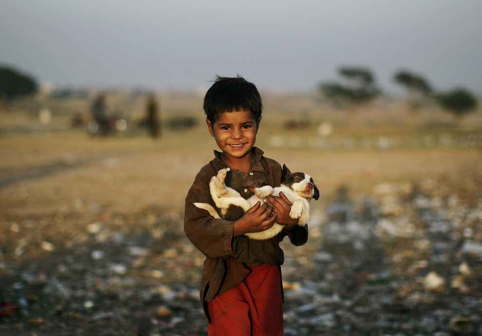 felixine:politics-war:Afghan refugee boy Samiullah Afsar, 5, carries a puppy he found in a pile of a garbage, on the outskirts of Islamabad, Pakistan.Photo: Muhammed Muheisen I can't