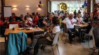 Mensen aan tafel die een kopje koffie of thee drinken tijdens het jubileumfeest