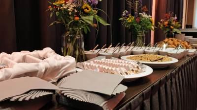 Schalen en kopjes met eten op een tafel met bestek en servetten erbij tijdens de politieke ontbijtbijeenkomst in Den Haag