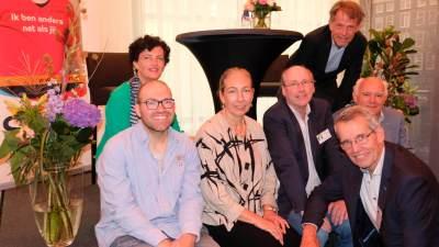 Groepsfoto van mensen die lachend op de rand van het podium zitten tijdens de politieke ontbijtbijeenkomst in Den Haag