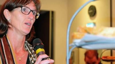 Foto van dichtbij van een vrouw die in een microfoon spreekt tijdens de politieke ontbijtbijeenkomst