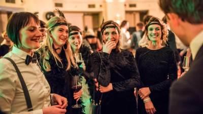 Illusionist Andrew Melia doet een goocheltruc vlak voor 5 dames die zijn verkleed in jaren 30-stijl. Alle dames lachen breeduit en 1 dame heeft haar hand voor haar mond van ongeloof