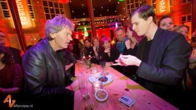 Illusionist doet een kaart truc vlakbij presentator Matthijs van Nieuwkerk die heel erg verbaasd zit te kijken