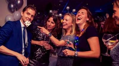 Illusionist Andrew Melia tovert een speelkaart uit zijn mond en drie dames moeten daar erg om lachen