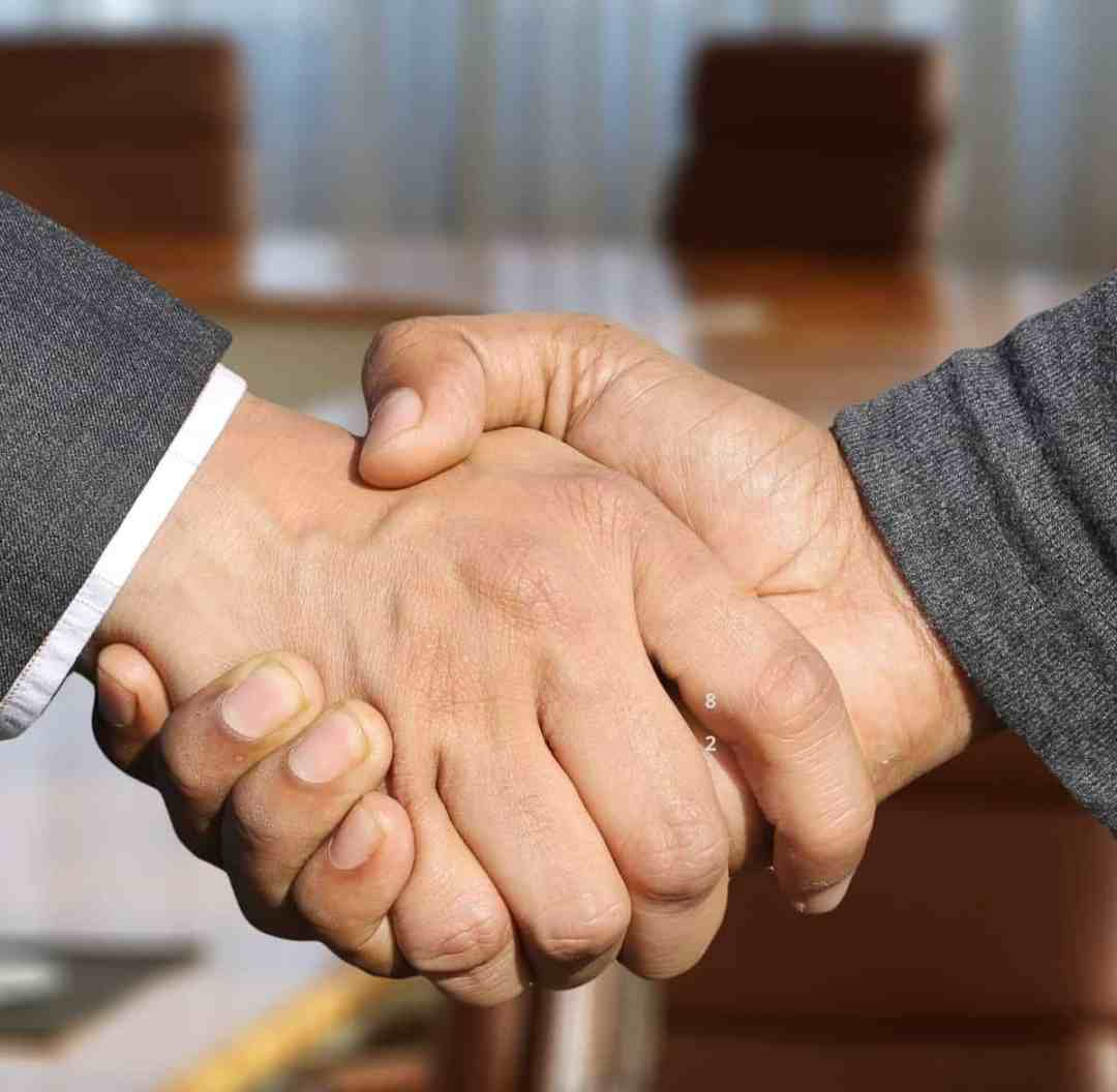 Twee handen van zakenmensen die elkaar schudden