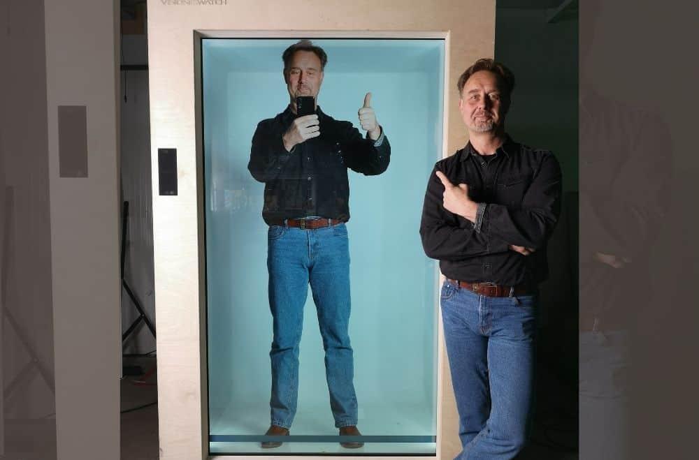Een man staat naast zijn eigen hologram projectie en wijst met zijn vinger