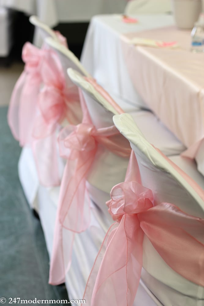 Chairs with white covers and pink bows