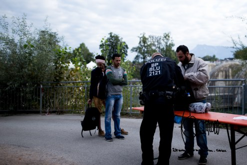 Asylum seekers get searched after crossing a bridge to Germany.