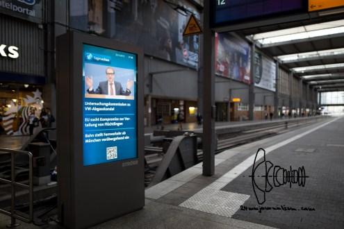 "A news sign says: ""Deutsche Bahn shuts down international service at Munich central station."""