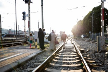 A refugee family sneaks off over traintracks at Munich Central Station.