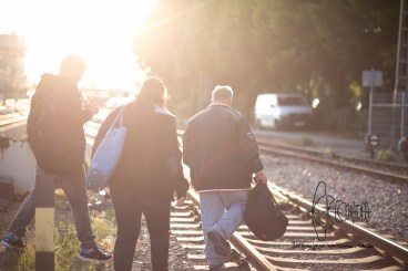 Three refugees try escaping registration process by sneaking off over traintracks.