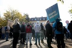 "Neonazis next to AfD demonstrators holding up a sign ""Stop Merkel!"""