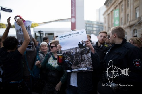 """Protestors hold up sign with the official motto of the day """"Overcome borders"""" and pictures from theEuropean borders."""