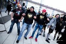 Chris Ares and PEGIDA Munich participants posing for photographers with hoodies that have the logo of the 'Bund Deutscher Patrioten'