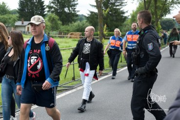 Participant on the way to the festival area with swastika shirt - about to get arrested by police.