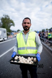 An Austrian tranlator/volunteer offers food to refugees, press and police.