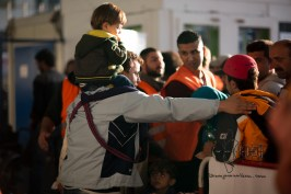 A young man with child on his shoulders at the intake of the refugee registration point.