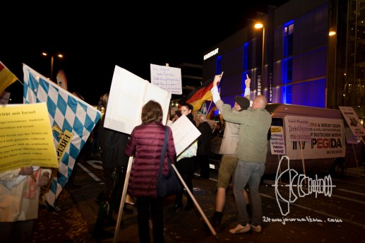 """After activists entered PEGIDA cage and showed a banner saying """"refugees welcome"""" PEGIDA members attack them with signs and grab them."""