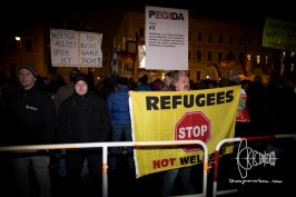 """A PEGIDA activist holds up a flag stating """"Refugees not Welcome"""" - right next to him neo-nazi party functionary and convicted terrorist Karl Heinz Statzberger."""