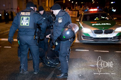 A single activist manages to reach PEGIDA route and tries to block police front vehicle from driving. Riot police carries him off the road.
