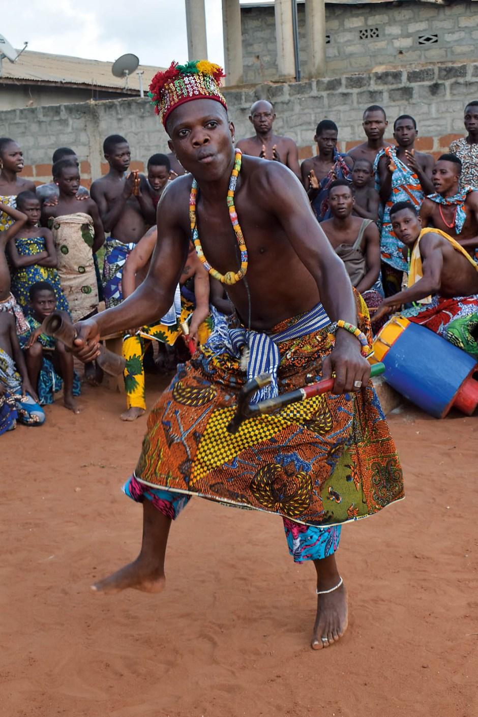 Das Dorf Hevie in der Nähe von Cotonou stimmt sich auf die Orakelzeremonie ein. Trommeln und rhythmisches Klatschen begleiten den Tänzer, der bei solchen Ereignissen auch in Trance fallen kann.
