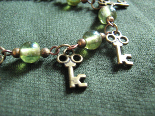 7 and a half inch /19 centimetre brass/coppertone findings, chain, pins, and key charms bracelet with green glass beads and acrylic accents.A cute little charm bracelet for the key to your heart. If your wrist is more narrow than the stated size please let me know, it can be easily shortened by up to an inch and a half.