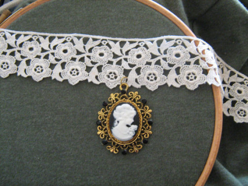 17 and a half inch / 44.5 centimetre vintage lace ribbon choker with gold plate fastenings, goldtone setting, black matte rhinestones, and a resin cameo. This unique dainty necklace is perfect for Classic or Sweet Lolitas, or anyone with an affinity for lace and cameos. The soft lace choker is easy on the skin and will sit just as well as a loose necklace over high-necked clothing as a choker on the wider neck.[here]