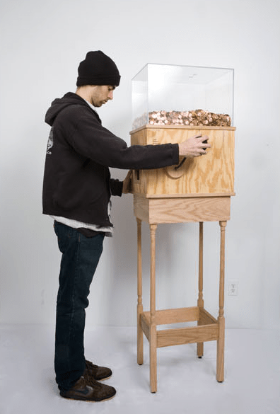 """Blake Fall-Conroy, """"Minimum Wage Machine,"""" 2008-2010. This machine allows anyone to work for minimum wage for as long as they like. Turning the crank on the side releases one penny every 4.97 seconds, for a total of $7.25 per hour. This corresponds to minimum wage for a person in New York. This piece is brilliant on multiple levels, particularly as social commentary. Without a doubt, most people who started operating the machine for fun would quickly grow disheartened and stop when realizing just how little they're earning by turning this mindless crank. A person would then conceivably realize that this is what nearly two million people in the United States do every day…at much harder jobs than turning a crank. This turns the piece into a simple, yet effective argument for raising the minimum wage. Here's a piece that another artist is working on that could also help inspire change in the U.S. government. He's trying to raise money to send every U.S. Senator a copy of Dr. Seuss' """"The Zax."""" They clearly should have paid more attention to stories about compromise like this in kindergarten. Indiegogo.com/TheZaxProject."""