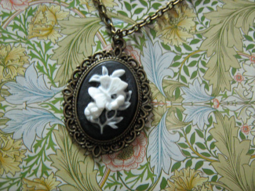 19 inch / 48 centimetre bronze cross chain necklace with coppertone and bronze findings, a brass setting, and resin cameo.A demure and sweet necklace for daytime wear, this pendant comprises a white-on-black cameo of a butterfly resting on some flowers, reminiscent of Regency porcelain work; the frame consists of very tight, compact scroll-work.click on source for listing