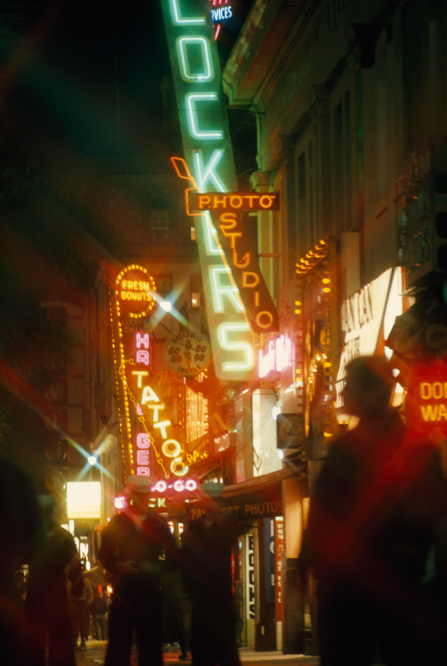 Neon signs blur the night scene as marines walk on the street in San Diego, California, July 1969.Photograph by James L. Amos, National Geographic