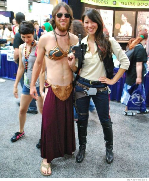 A lean young pale-skinned man of European appearance with shoulder length hair and a beard wears a skimpy Slave Leia costume; beside him is a young woman of East Asian appearance dressed in Han Solo's classic outfit of blue trousers with Corellian stripe tucked into cavalry boots, pale shirt with a dark waistcoast and raygun holster slung on hip