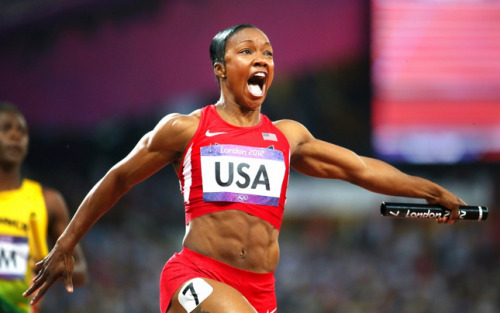 Carmelita Jeter, holding the baton in her left hand, crosses the finish line after completing the 4 by 100M relay. Her arms are spread, her abs, which are flexed, are on full display. She has a giant smile on her face, her mouth wide open as she sees the screen that displays her team's time.