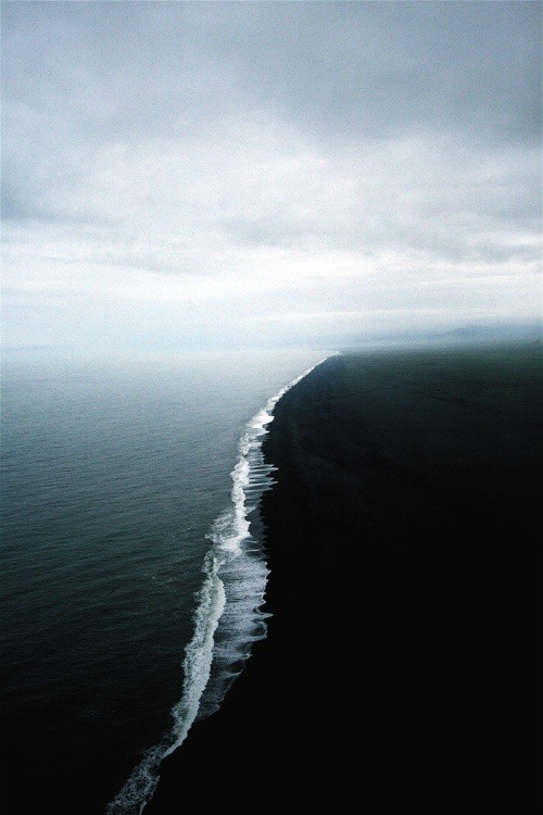 Two seas of different densities meet. There is a white water line along the meeting point. One sea is a very dark color, and the other is a gray-blue. Taken off the Alaskan coast.