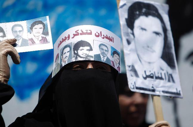 "Basma Ali Khan, holds posters of her disappeared father during a protest held as part of ""The Walls Remember"" campaign to put focus on people who have disappeared in what is known as the ""forced disappearance"", in Sanaa September 27, 2012. Yemenis are using street art to lobby the government to tell what happened to hundreds of people who disappeared in years of political turmoil, but even their images on the walls have troubled powerful figures who sought to remove the graffiti. The headband reads: ""The walls remember their faces."" [Credit : Khaled Abdullah/Reuters]"