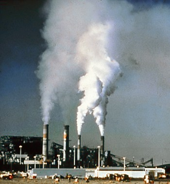 A power plant with four smoke stacks emits large amounts of billowing greenhouse gases.