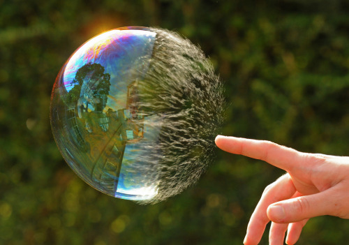 A soap bubble halfway through being popped. Half is intact and the other half consists of threads of soap still in the shape of a bubble.