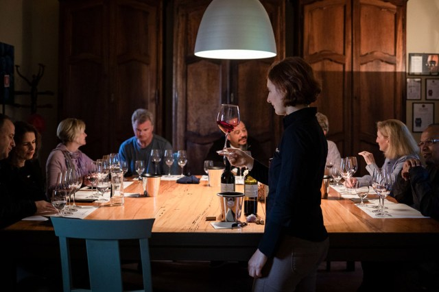 Group tasting red wines at a table
