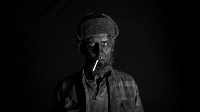 Portrait of a Woodsman wearing a deerstalker hat and cigarette in mouth. Face totally blackened