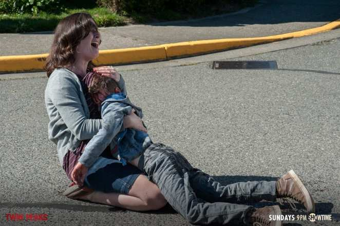 A mother screams as she holds the dead body of her son who has been hit by a truck