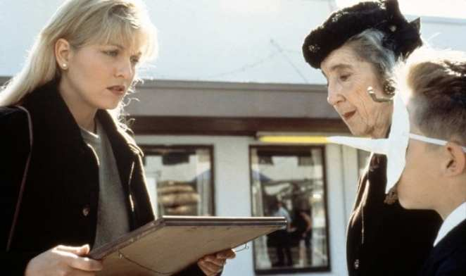 Mrs Tremond and her grandson who is wearing a mask, give Laura Palmer a picture of a doorway, while they stand outside the Double R Diner