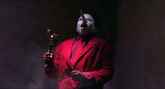 The Jumping Man Twin Peaks squeals in a smokey room, wearing a red suit, white face with pointed nose and carrying a small wand like branch